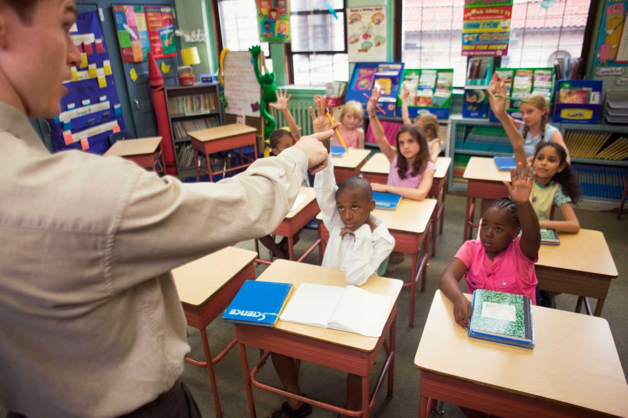 Kids-raising-hands-in-class-camera-from-front-of-class-2123x1413
