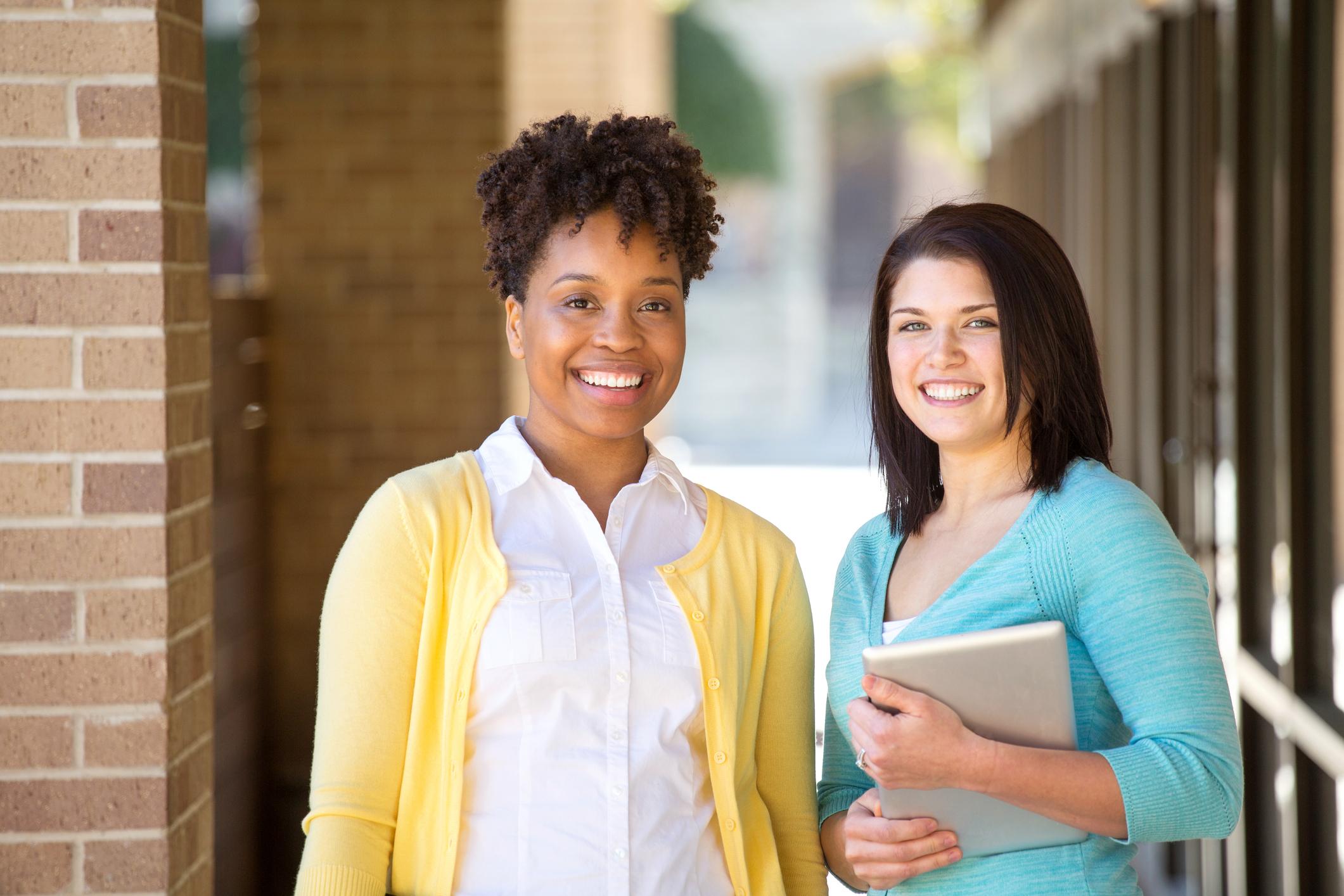 Business women standing outside an office building.