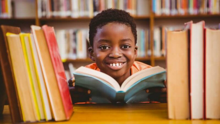 a6dd7a64c9a27112a41b9d34a66cbc32_Cute-boy-reading-book-in-library-2650x1767-2650-1491-c-90-optimized