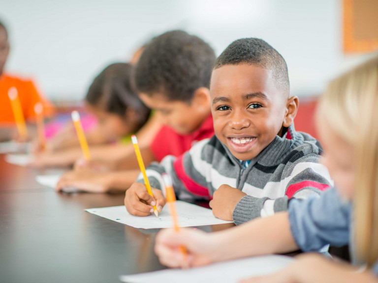 Young-Boy-Sitting-Happily-in-Class-2650x1769
