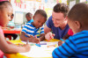 Volunteer-teacher-helping-a-class-of-preschool-kids-drawing-484793580