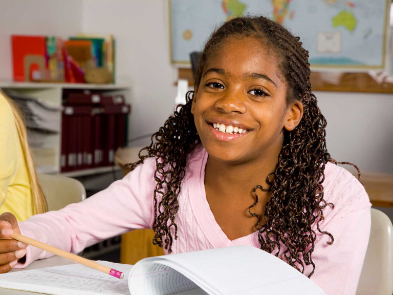 Young-student-at-desk-with-book-smiling-at-camera-1698x1131