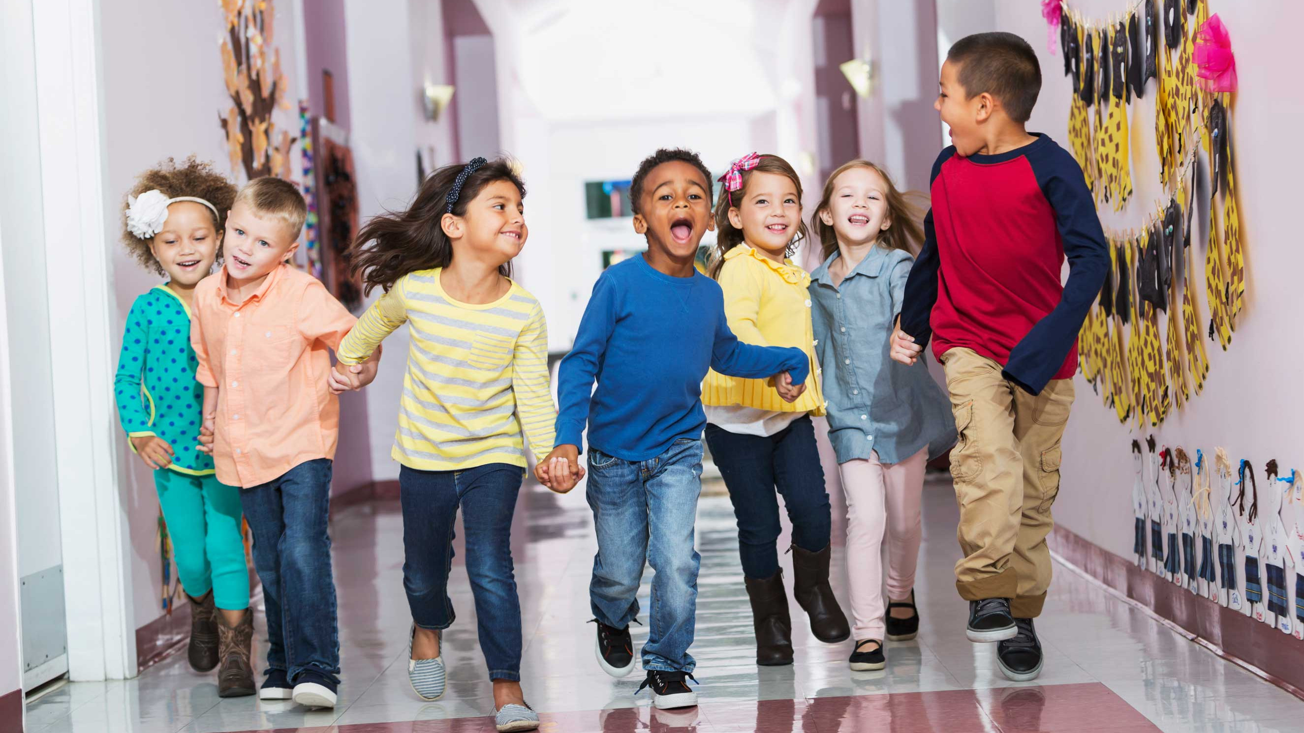 Multiracial-group-of-preschoolers-running-down-hallway-2650x1767